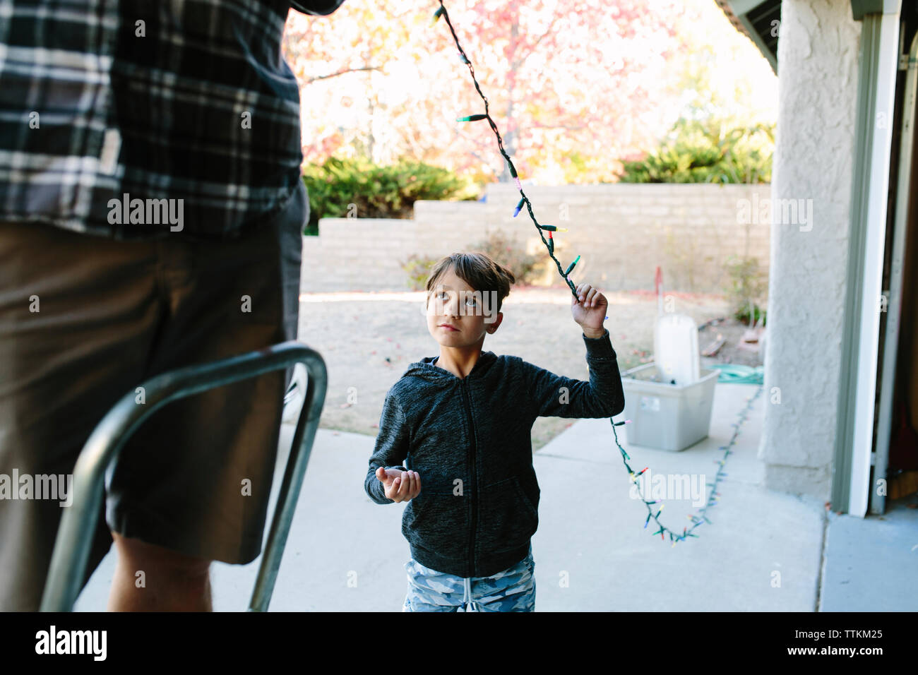 Son looking at father hanging colorful string lights on house during Christmas Stock Photo