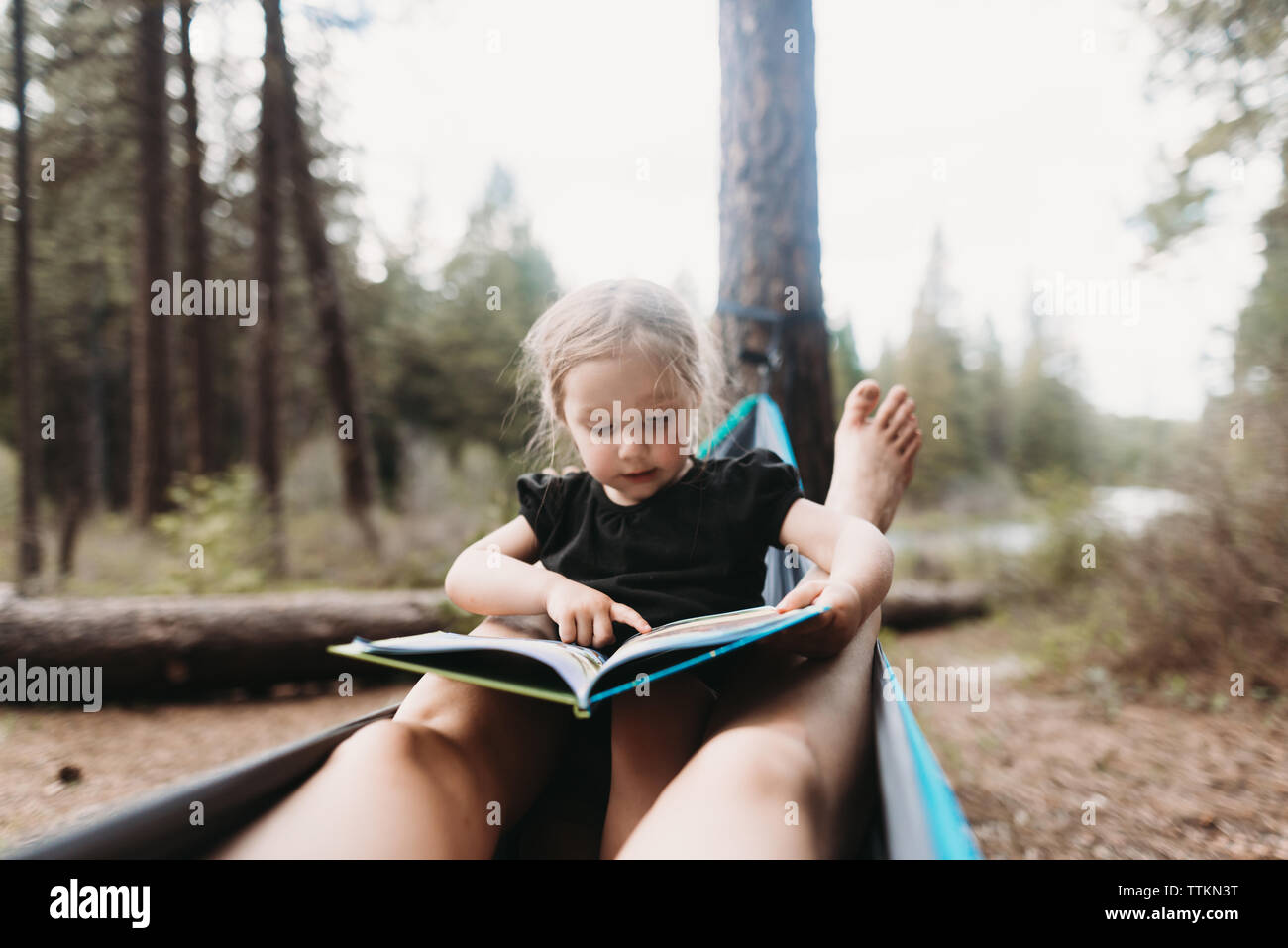 Cropped legs of mother around daughter reading story book in hammock at campsite - Stock Image