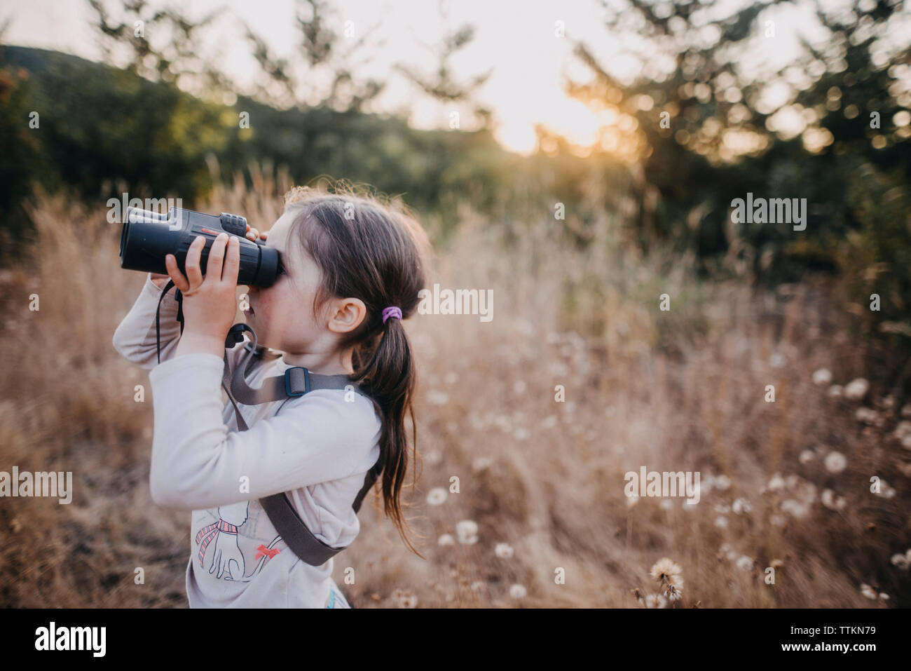 Side view of girl looking through binoculars while standing on field - Stock Image