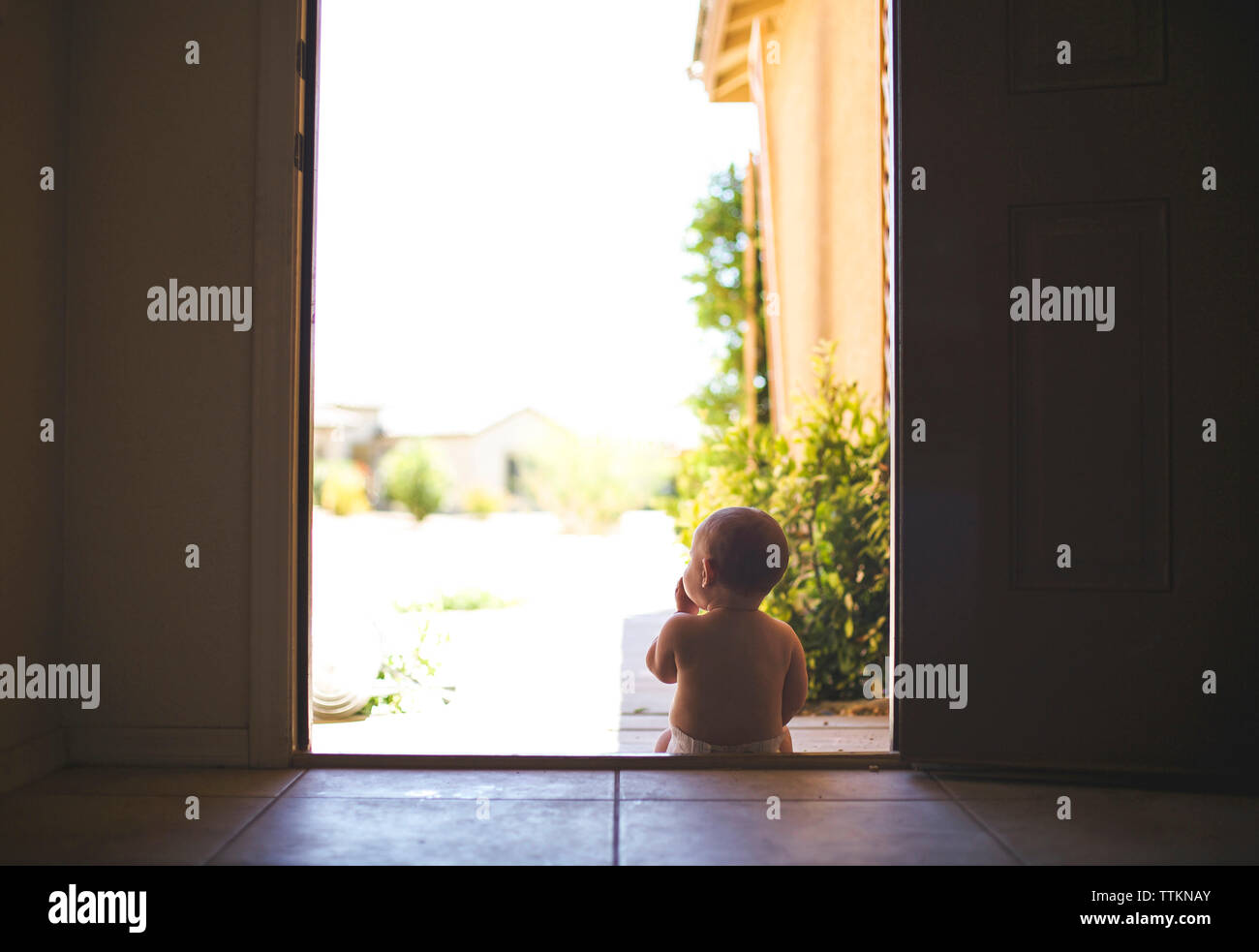 Rear view of baby sitting on doorway during sunny day - Stock Image