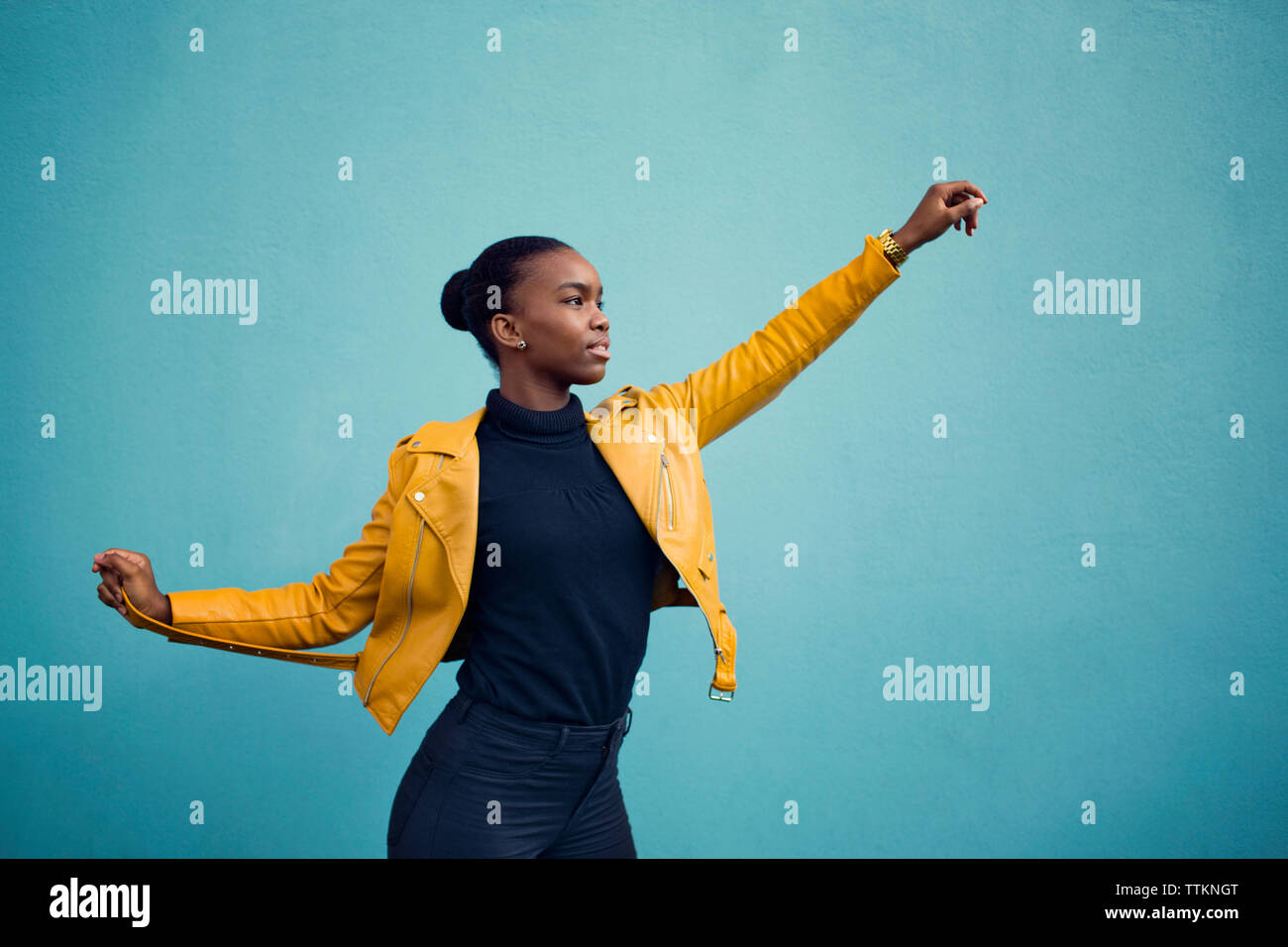 Confident fashion model standing with arms outstretched against blue wall Stock Photo
