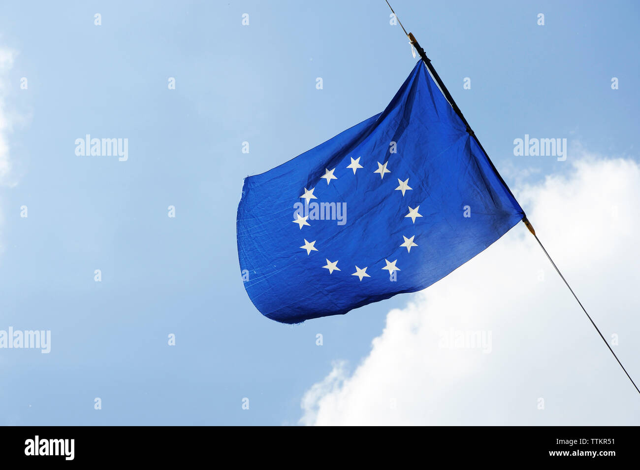 A flag of european union is flying on a background of blue sky with white clouds - Stock Image