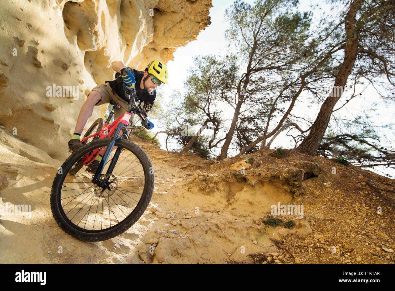 Cyclist descending through a very technical area of sandstone Stock Photo