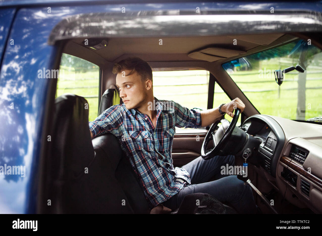 Man looking over shoulder while driving pick-up truck seen through window - Stock Image