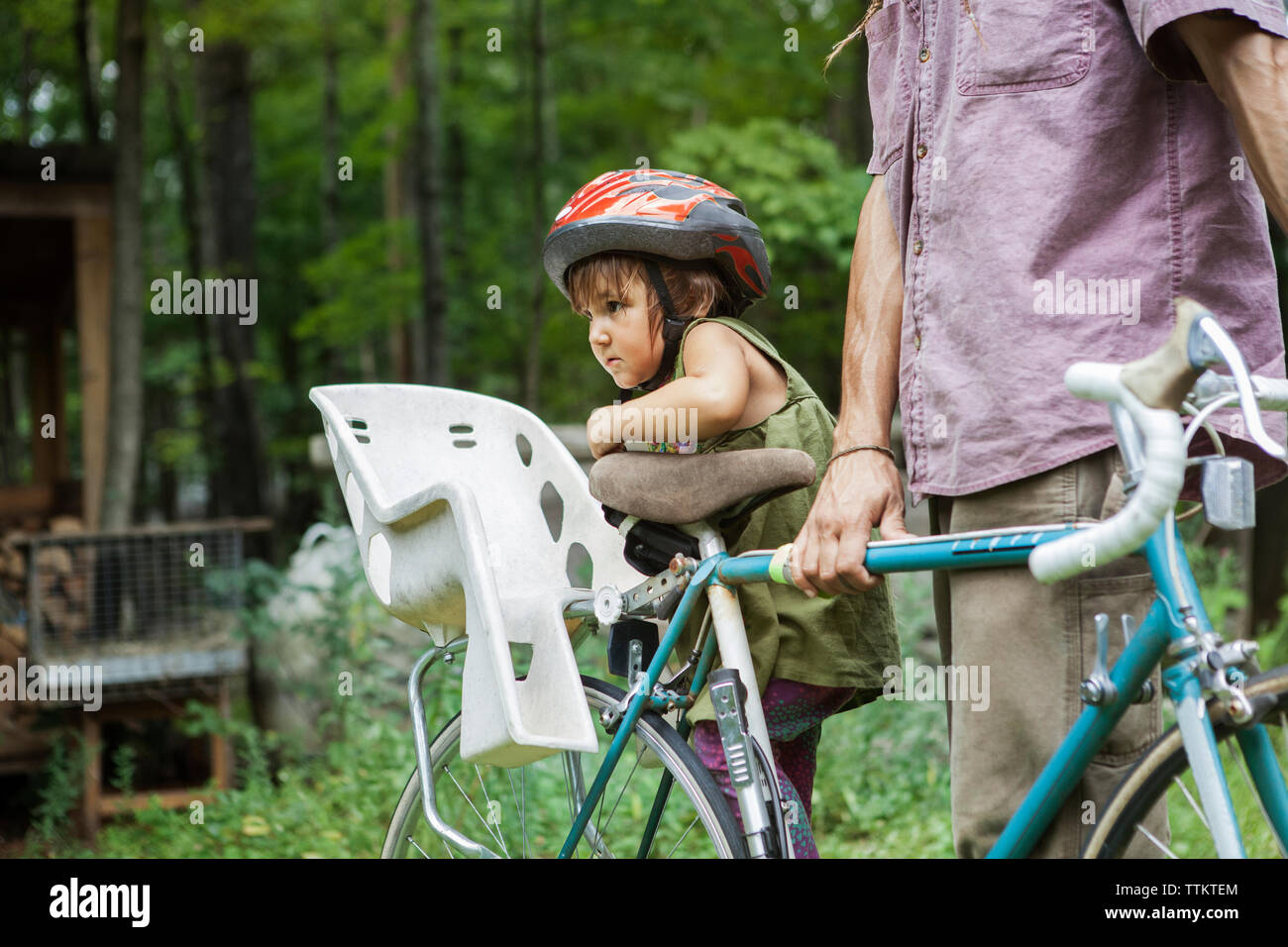Midsection of man with daughter on bicycle in backyard - Stock Image
