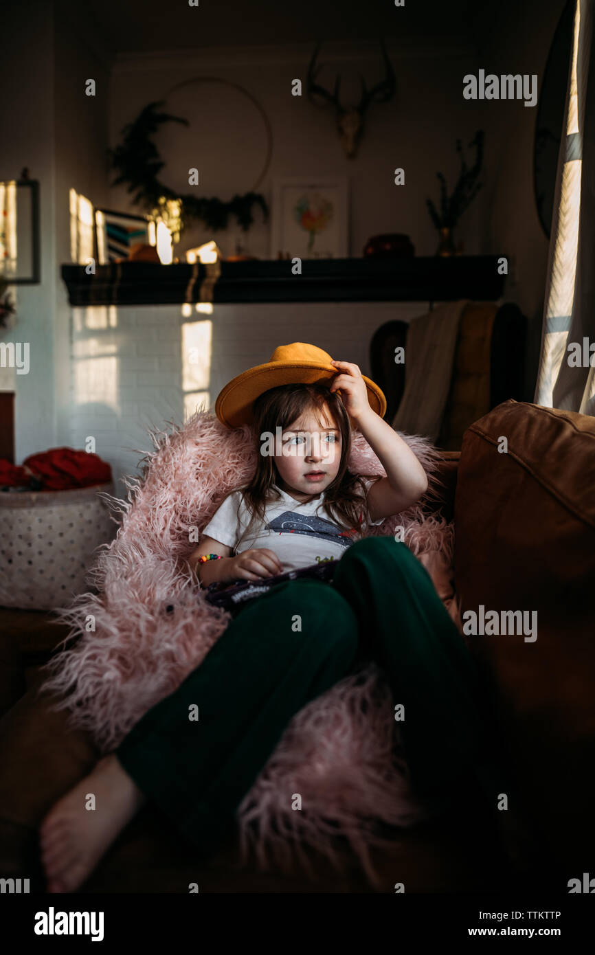 Girl looking out window with yellow hat in home Stock Photo