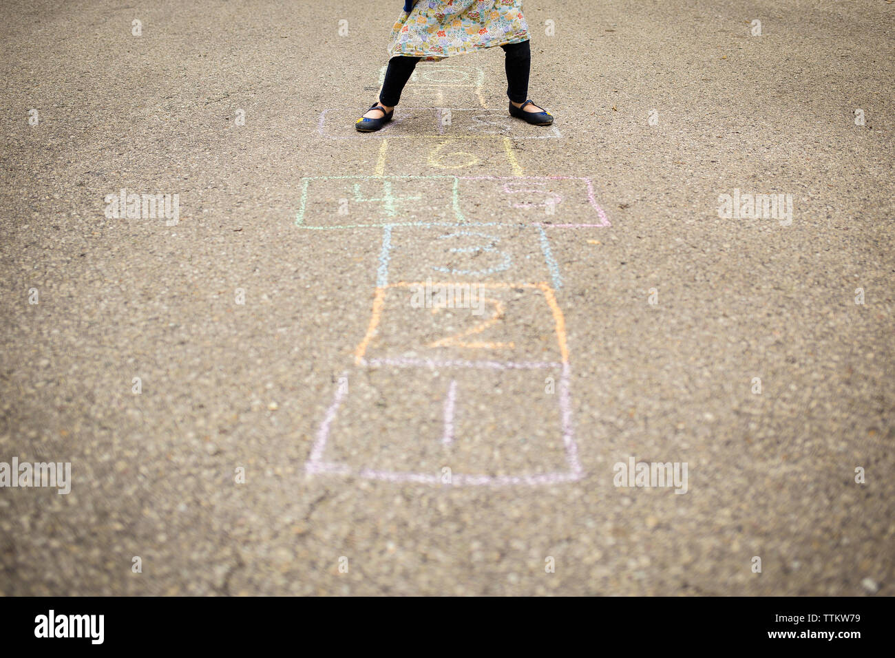 Low section of girl playing hopscotch on street - Stock Image