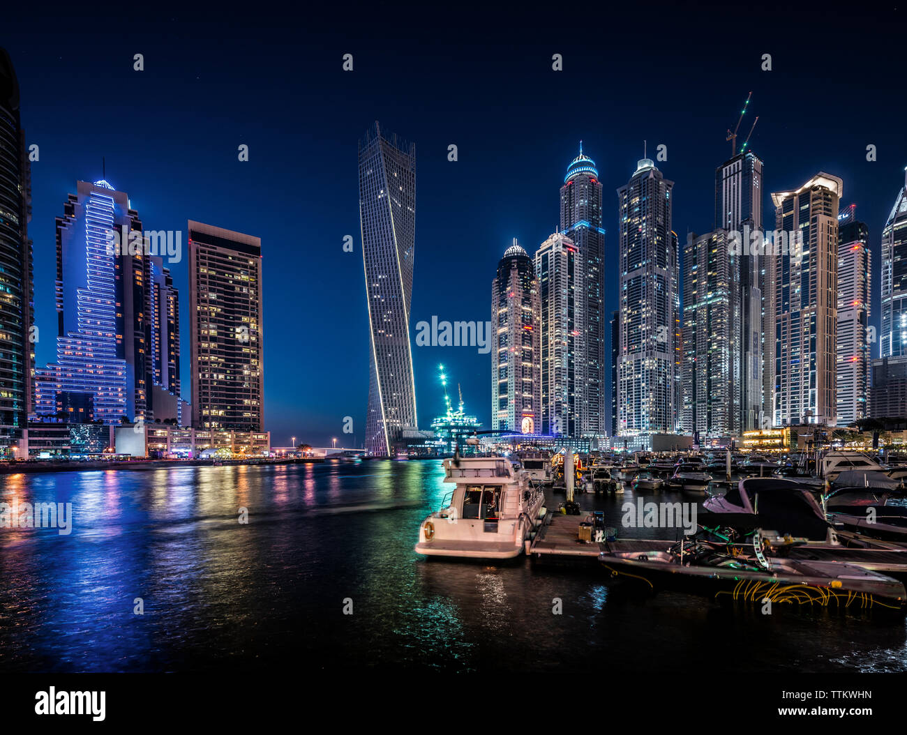River and illuminated cityscape against blue sky at night - Stock Image