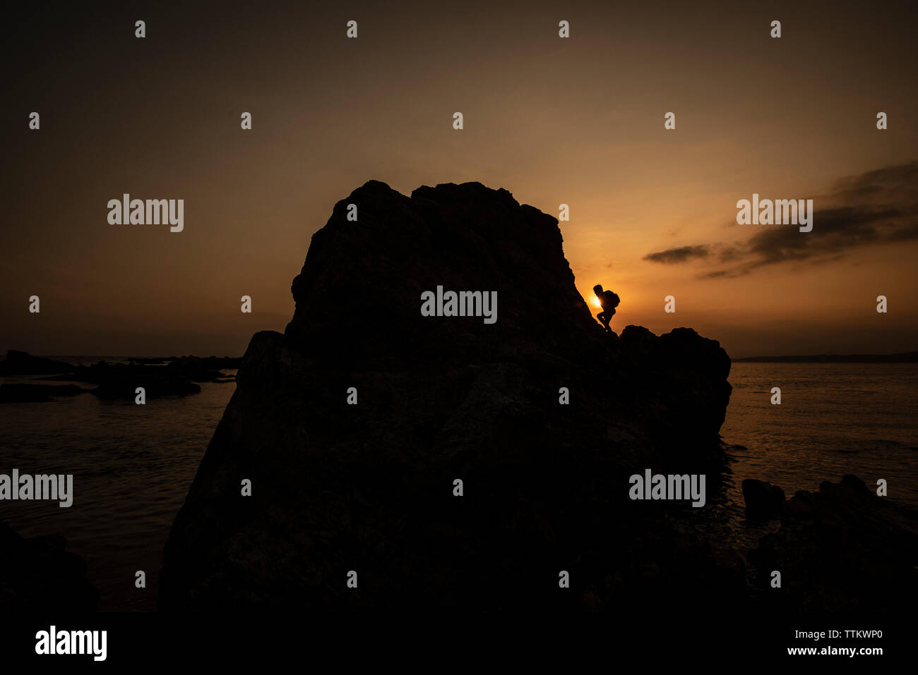 Silhouette child climbing on rock at beach against sky during sunset - Stock Image