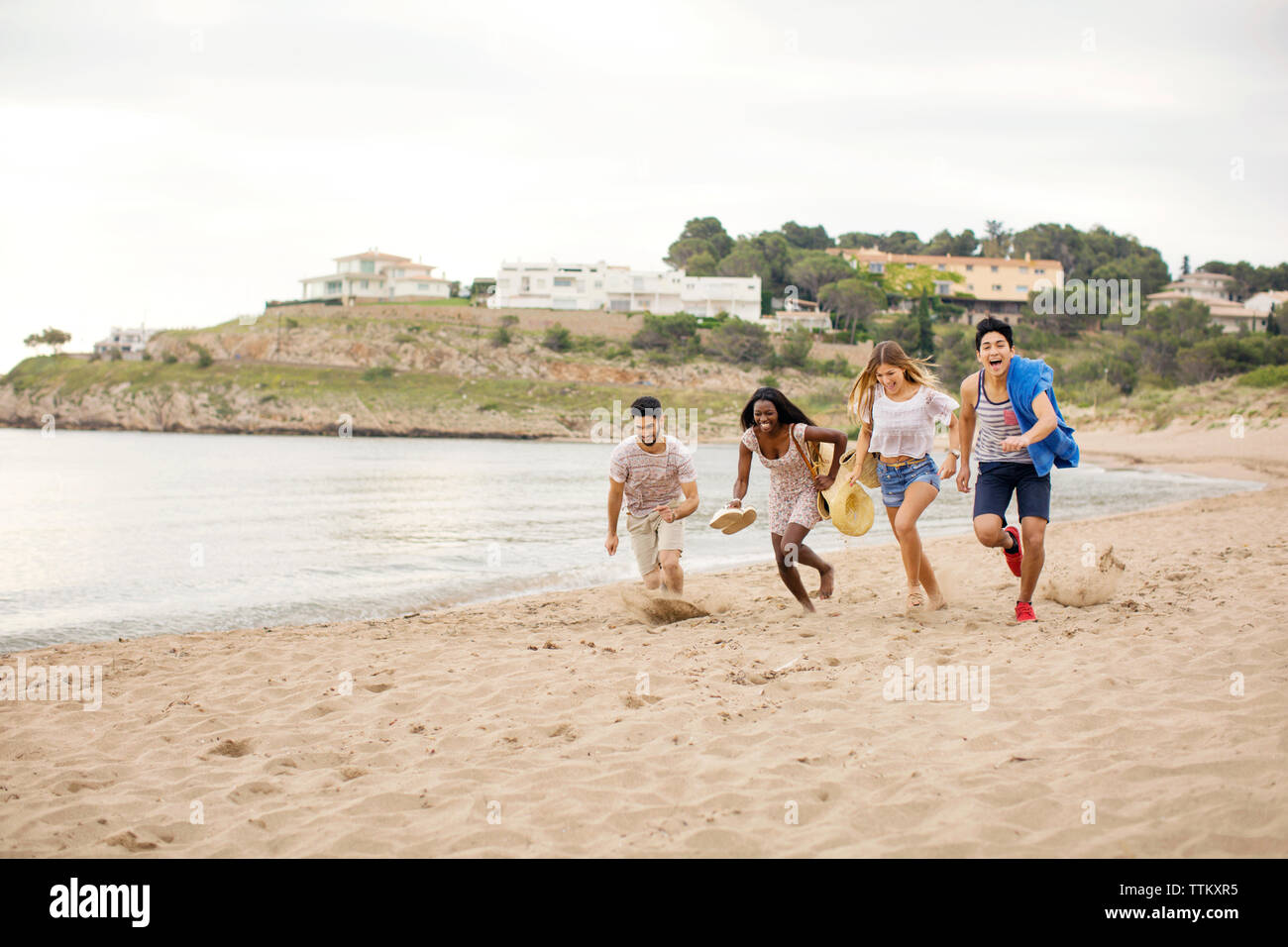 Playful friends running on shore at beach during vacation - Stock Image