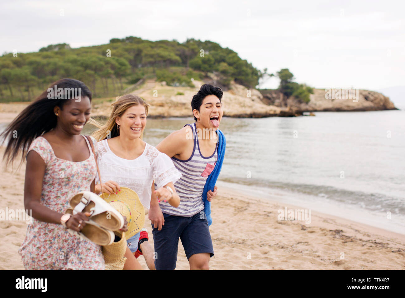 Cheerful friends running on beach during vacation - Stock Image