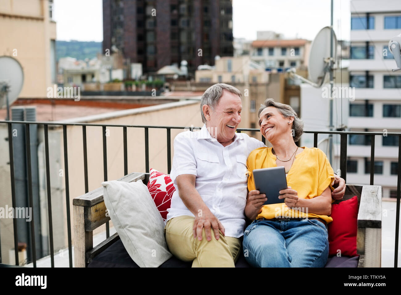 Cheerful senior couple spending leisure time on terrace - Stock Image