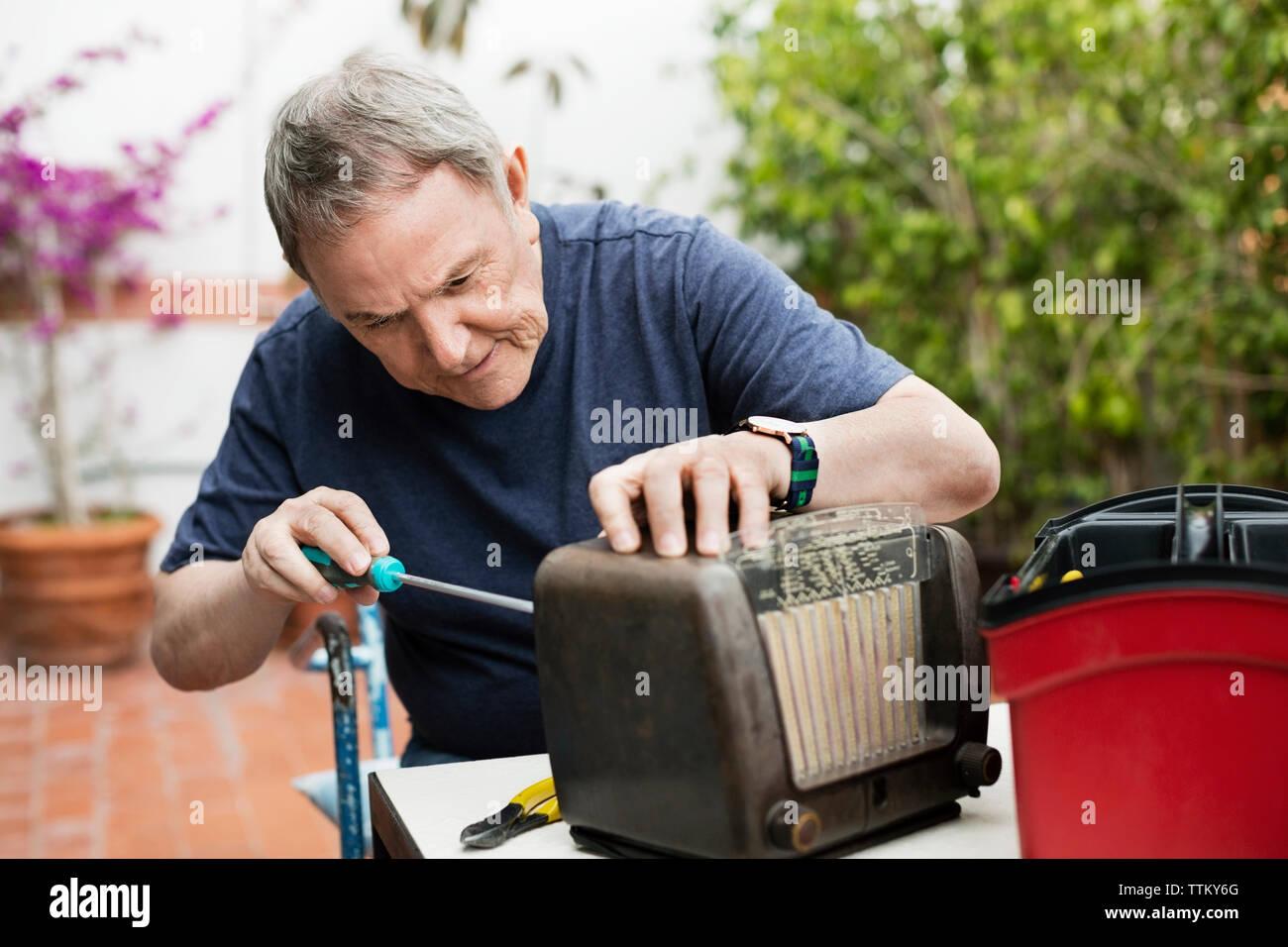 Senior man repairing old-fashioned radio at yard Stock Photo