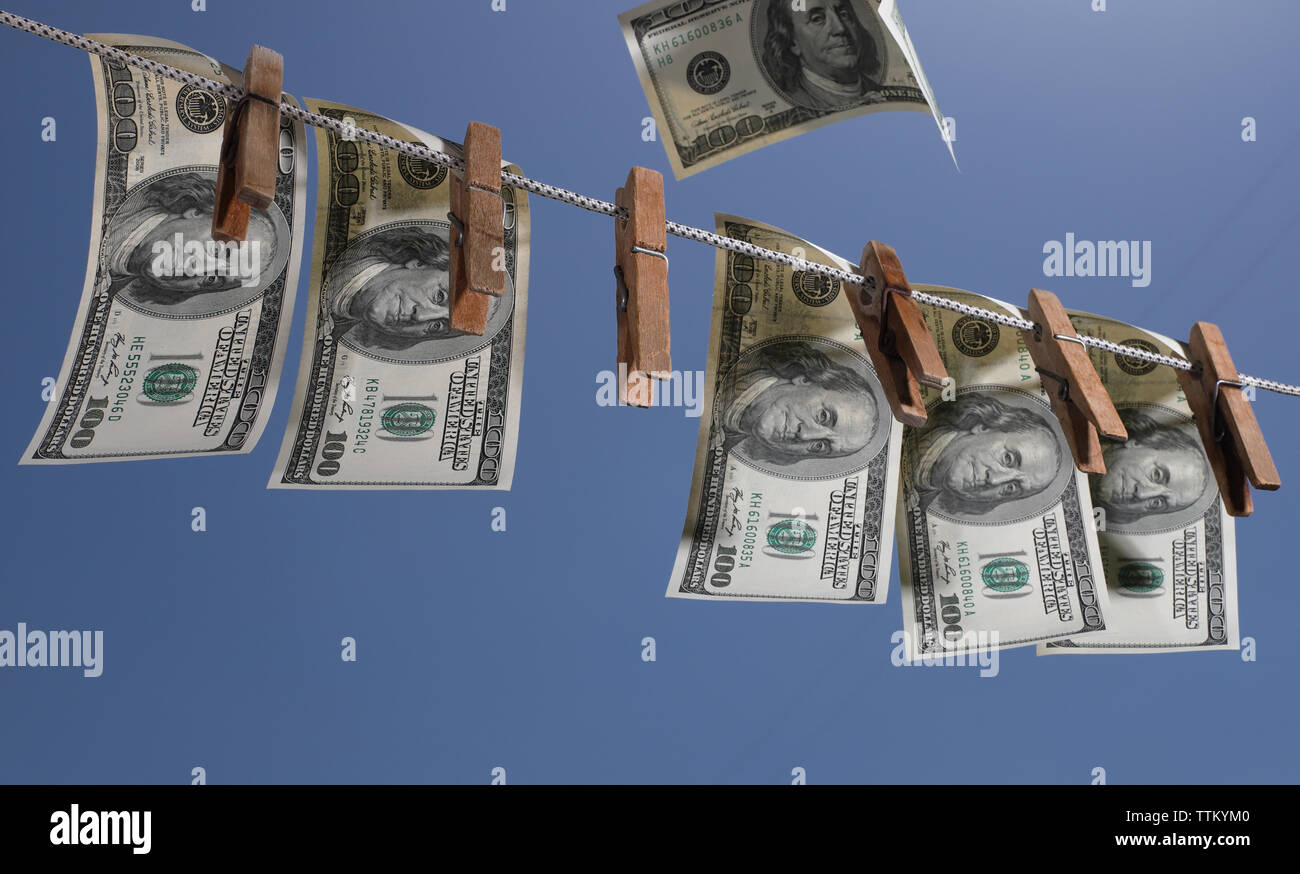 Money Hanging On a Clothesline With Old Wooden Clothespins. The symbol of offshore investments, financial crimes and money laundering. - Stock Image