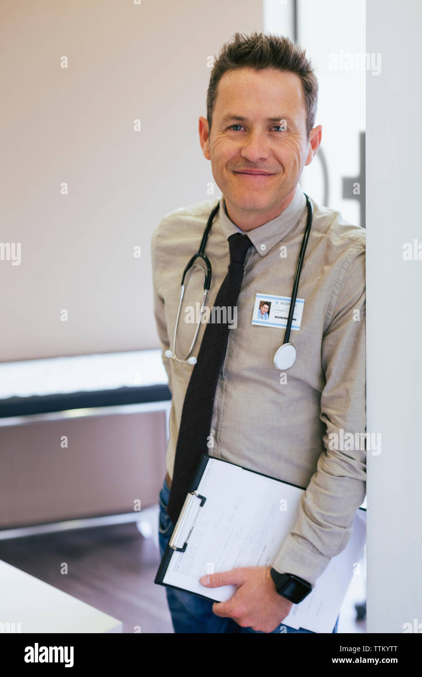 Portrait of smiling doctor leaning on wall at hospital - Stock Image