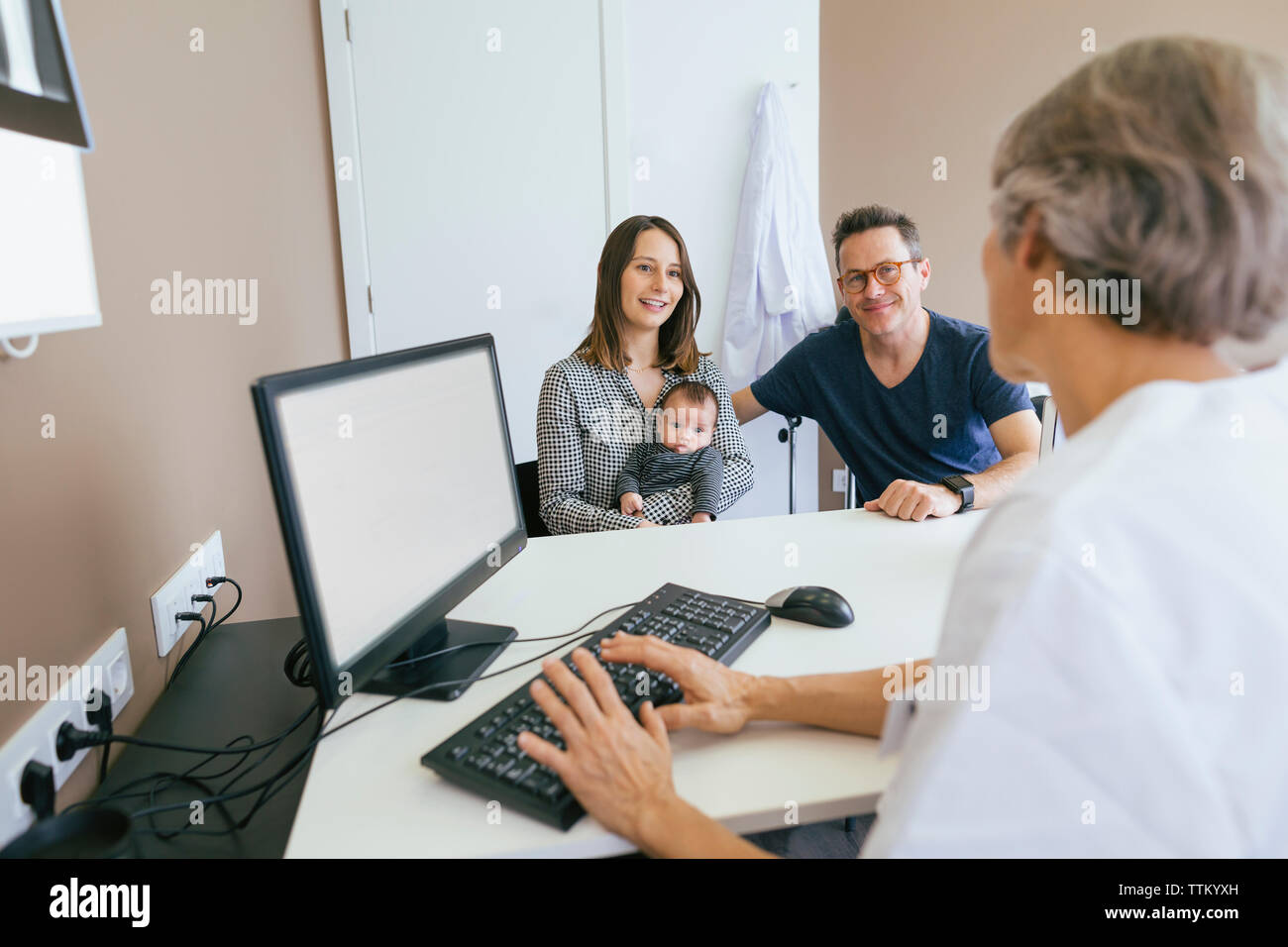 Happy family discussing with doctor at medical clinic Stock Photo
