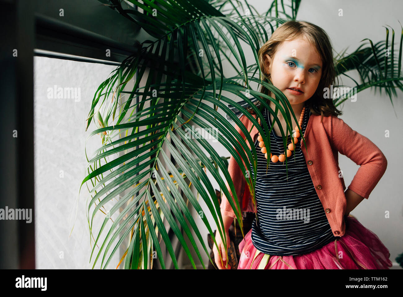 Portrait of girl with messy eyeshadow standing by plants at home - Stock Image