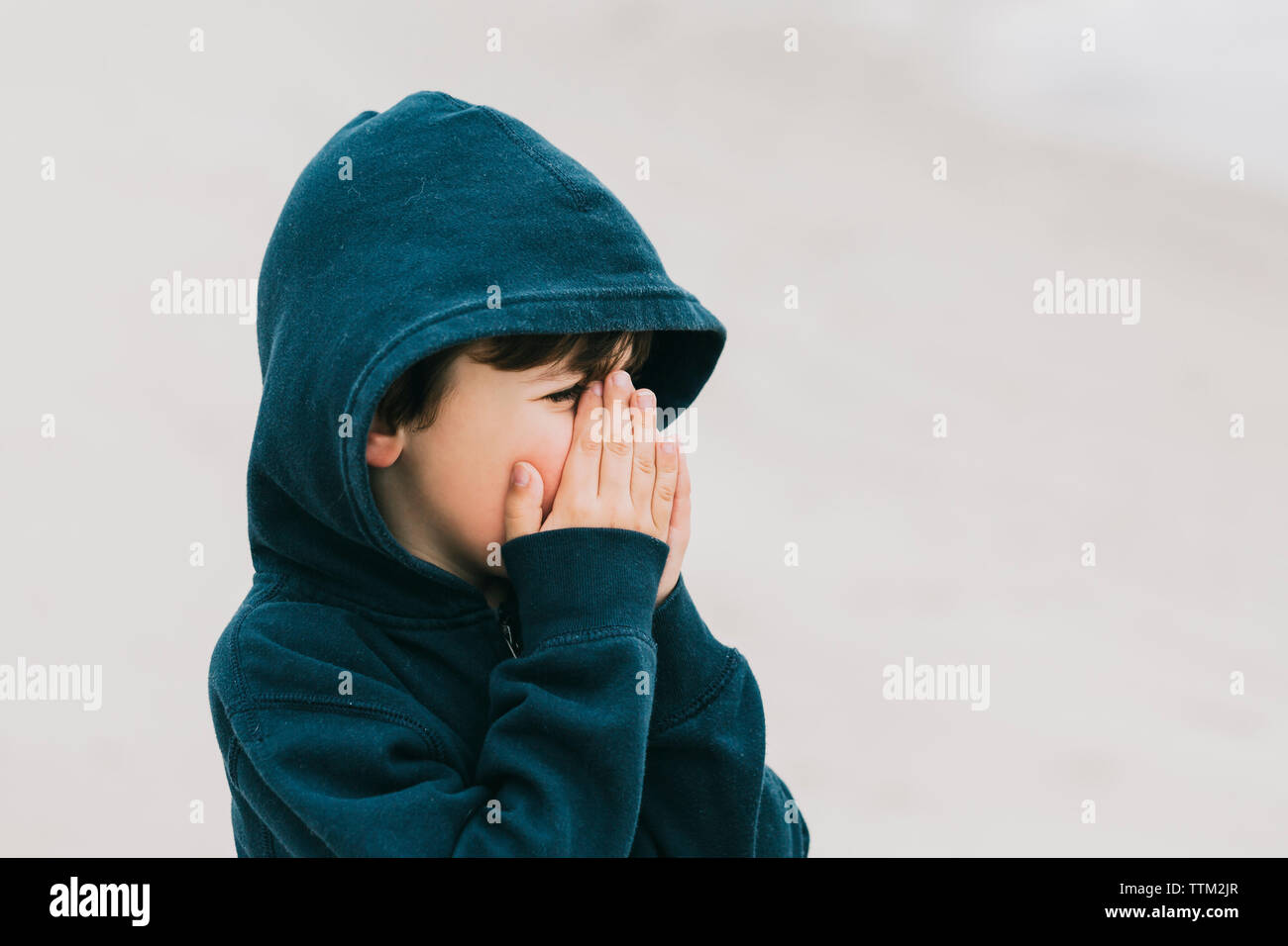 Boy with hands covering mouth standing at beach Stock Photo