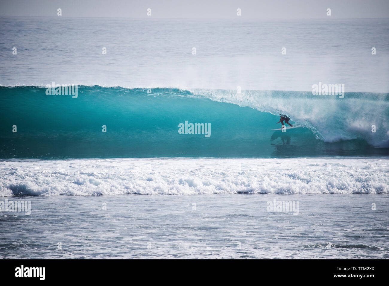Person surfing in rolling surf at Mentawai Islands - Stock Image