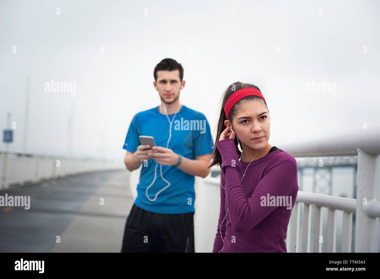 Confident female athlete wearing earphones while standing with friend on Bay Bridge Stock Photo