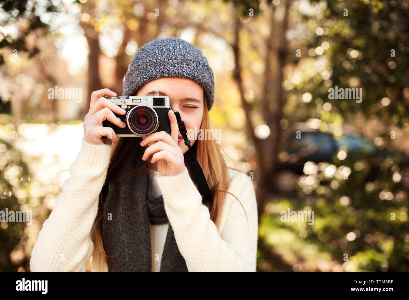Girl photographing with camera against trees - Stock Image
