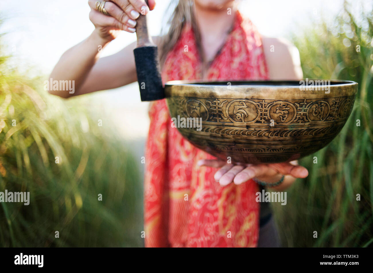 Cropped image of woman holding Tibetan singing bowl - Stock Image
