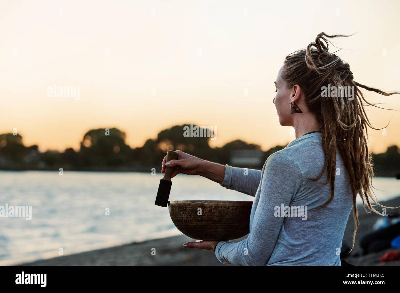 Woman holding Tibetan singing bowl at beach during sunset - Stock Image