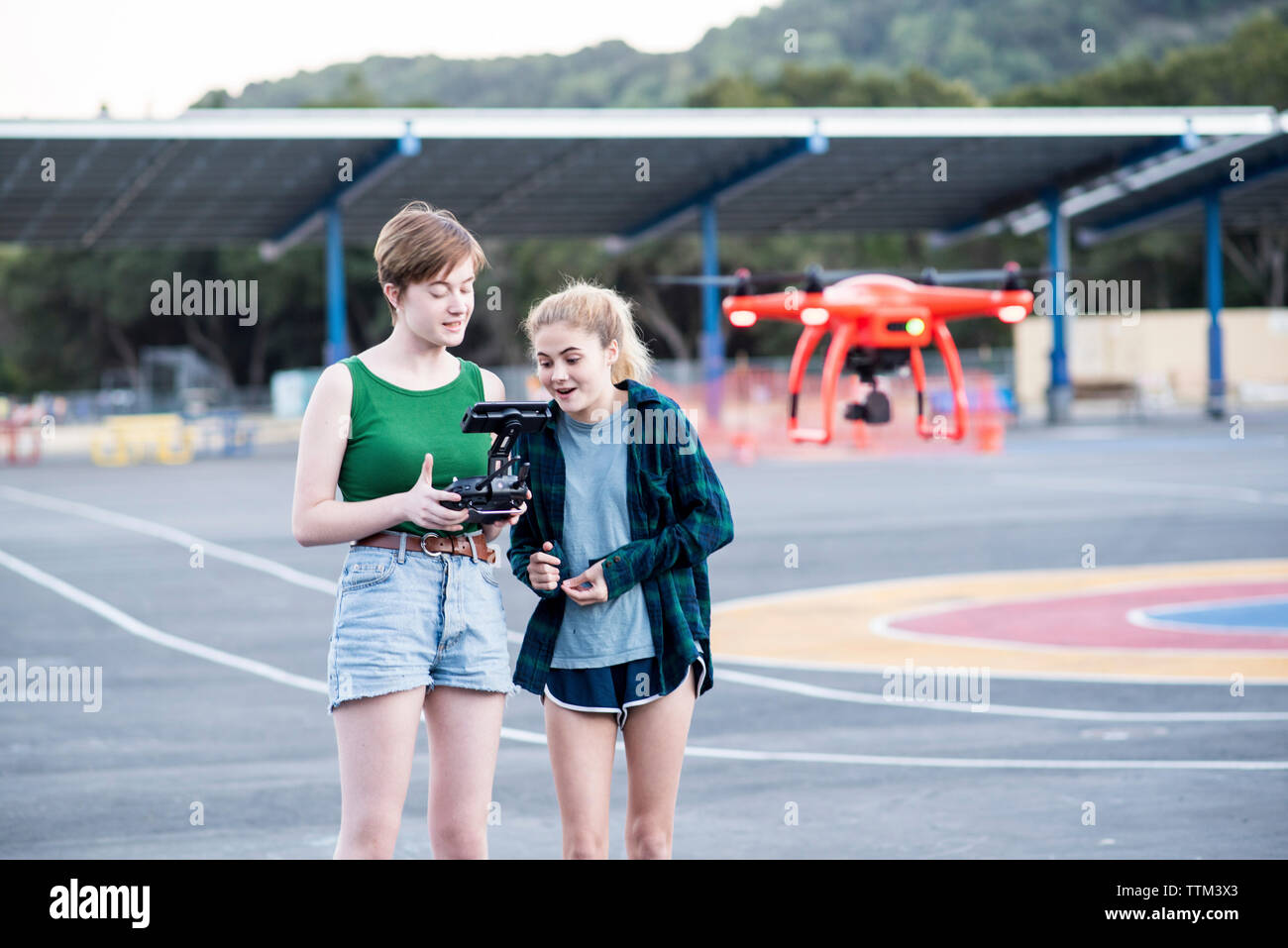 Teenage friends operating quadcopter at park - Stock Image