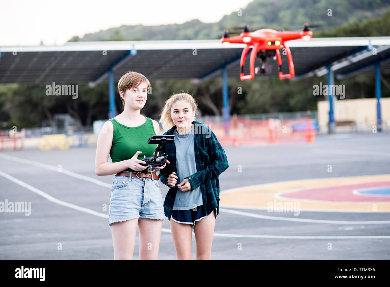 Friends operating quadcopter while standing at park - Stock Image
