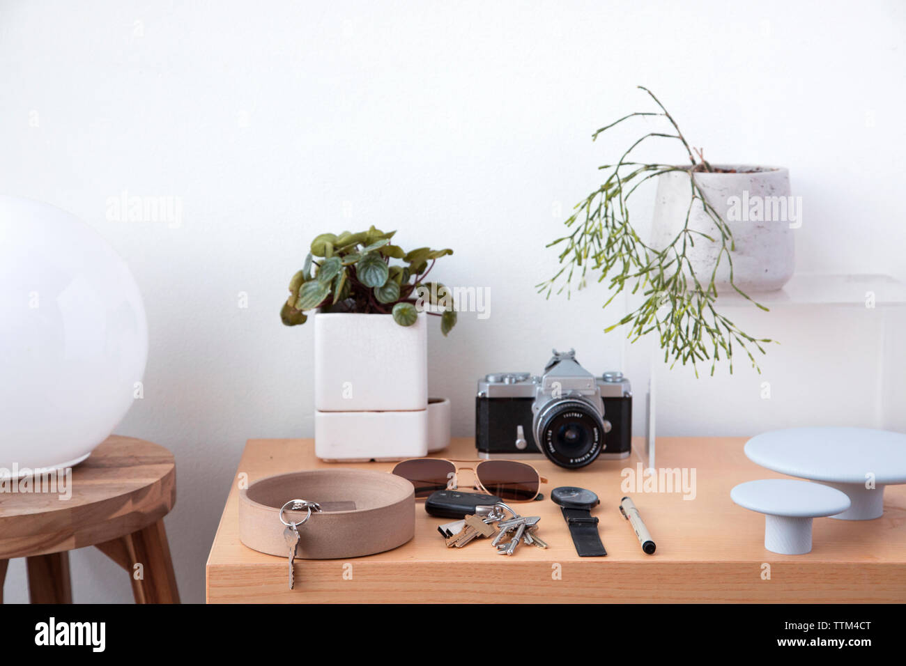 Various objects on wooden table against white wall at home - Stock Image