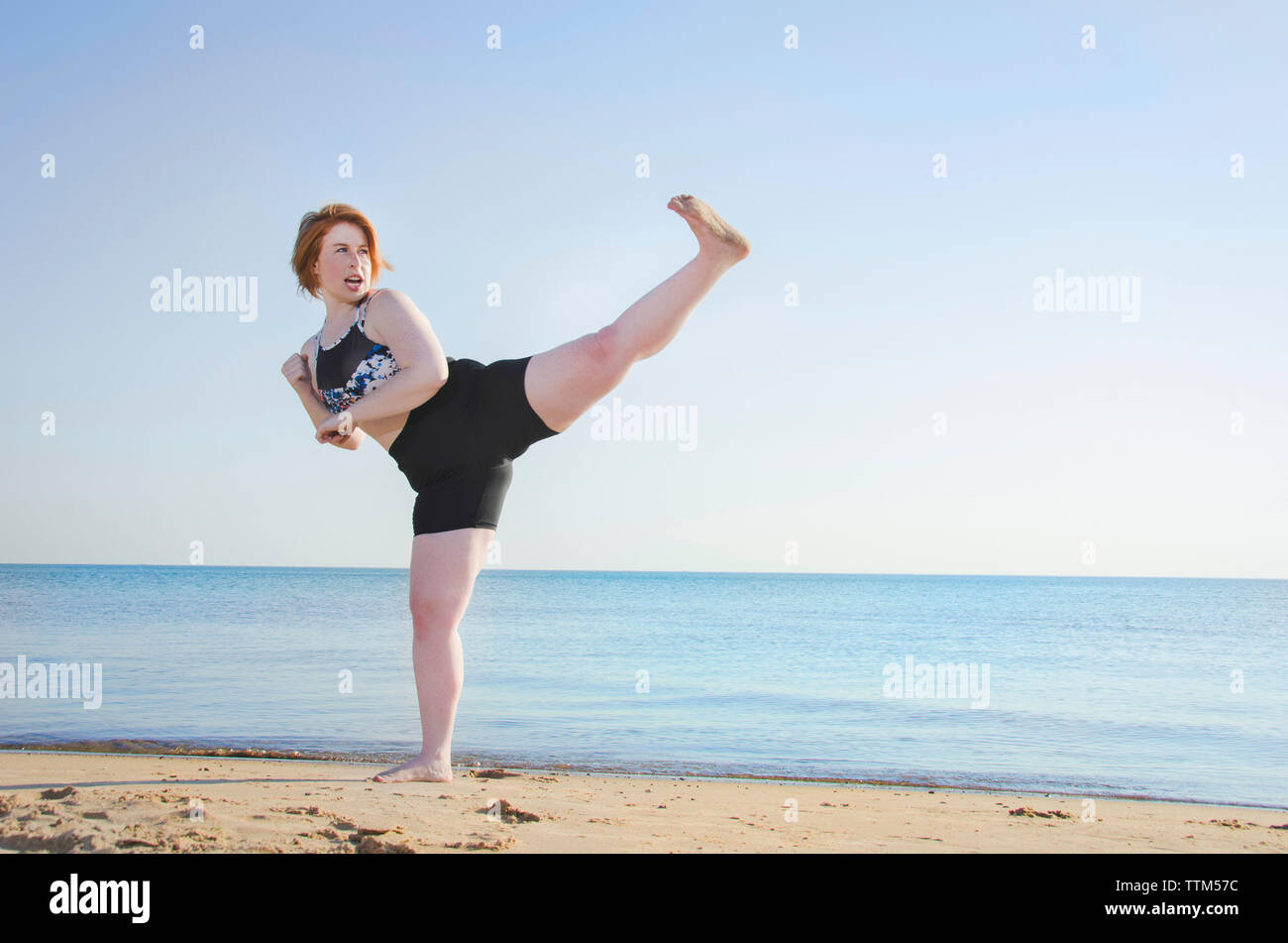 Woman practicing kickboxing at beach against clear sky - Stock Image
