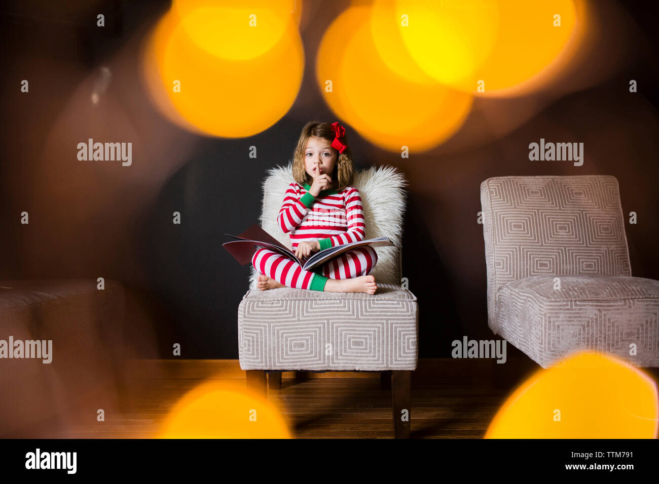 Portrait of girl with finger on lips and book sitting on chair at home - Stock Image