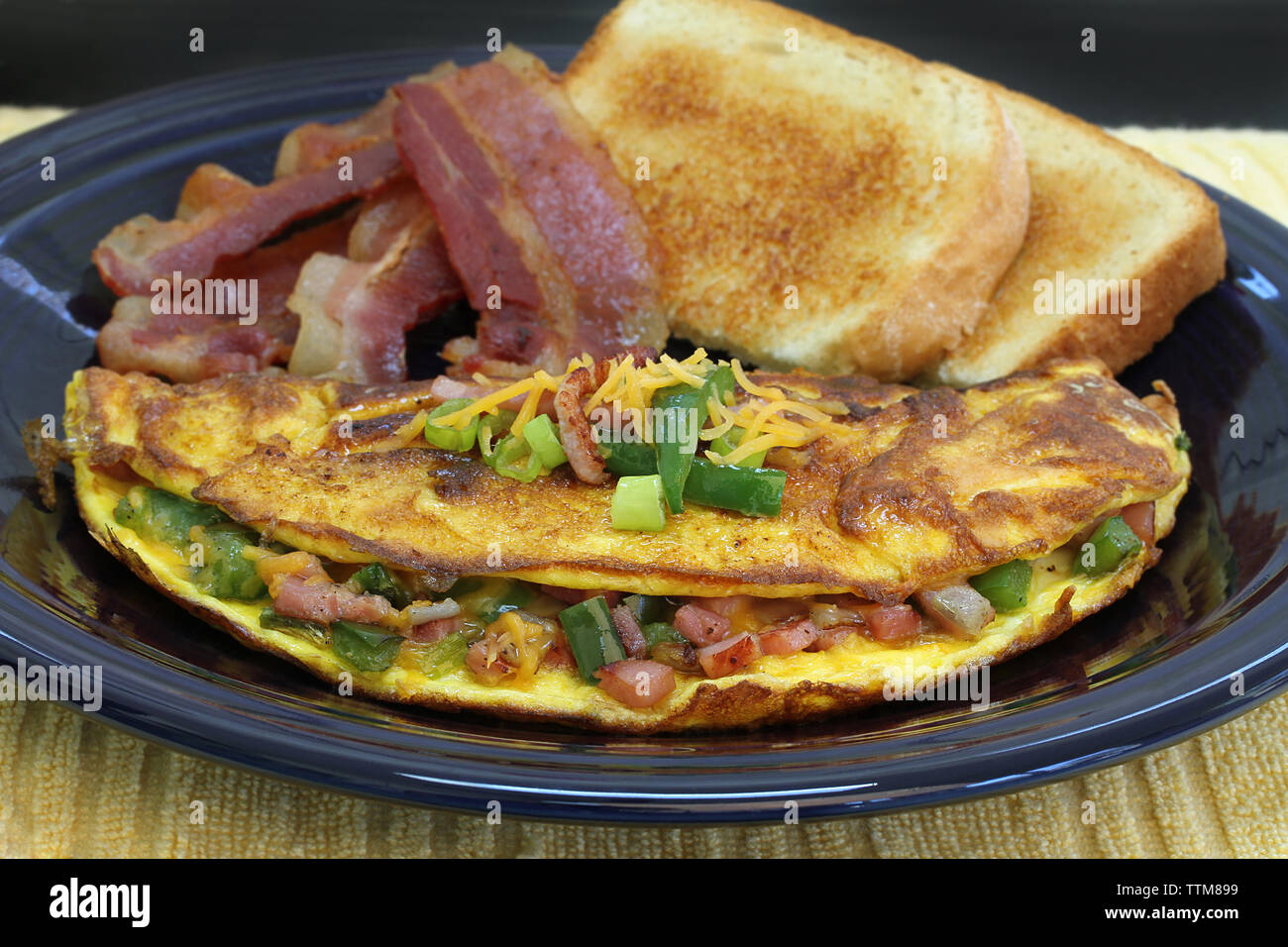 Macro view of a Western or Denver omelet with sides of bacon and toast.  Selective focus on omelet front. - Stock Image