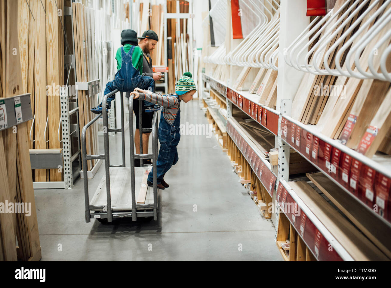 Father standing by sons playing on push cart at factory - Stock Image