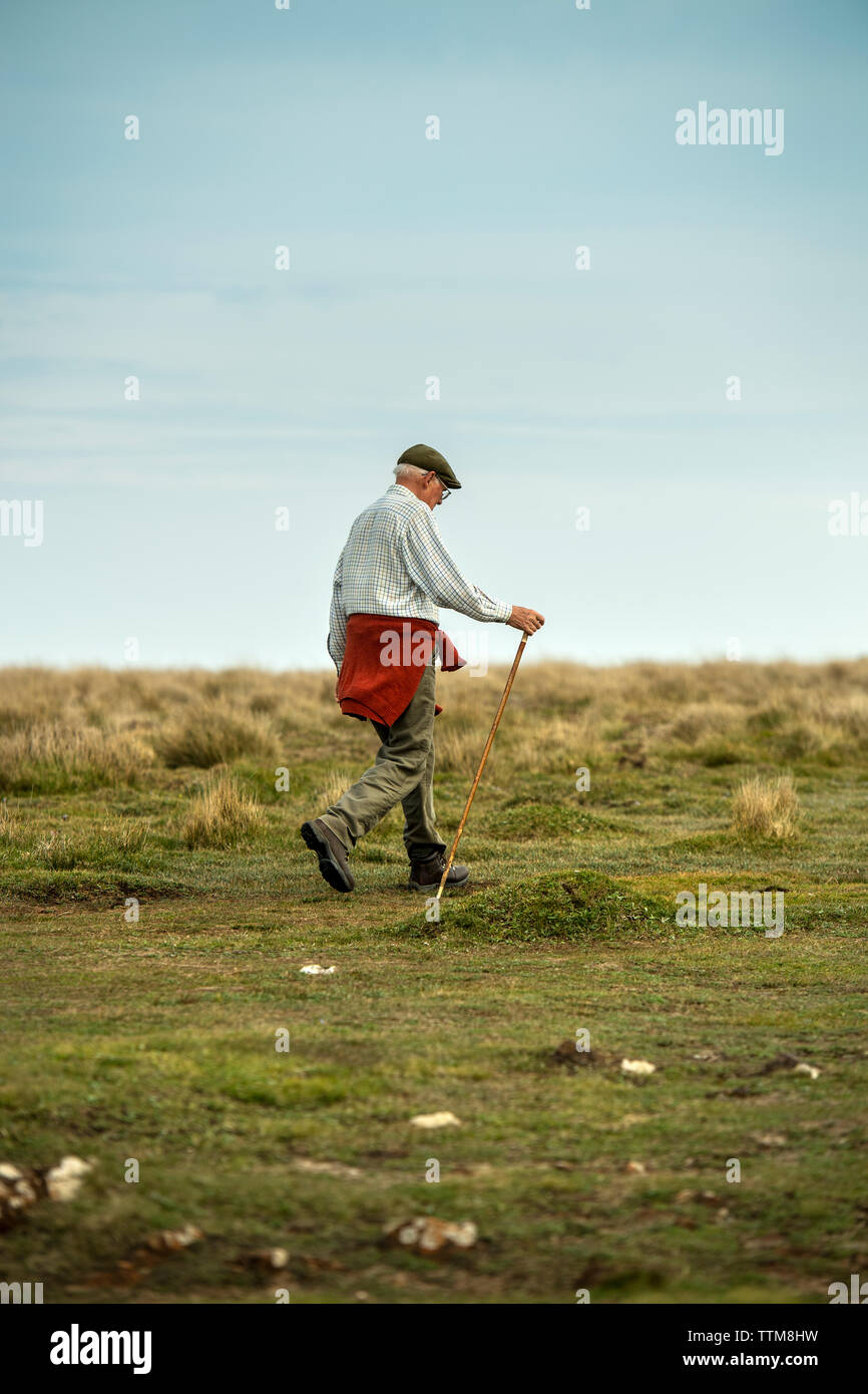 Elderly man walking on the South West Coast Path near the Lizard in Cornwall, England, UK - Stock Image