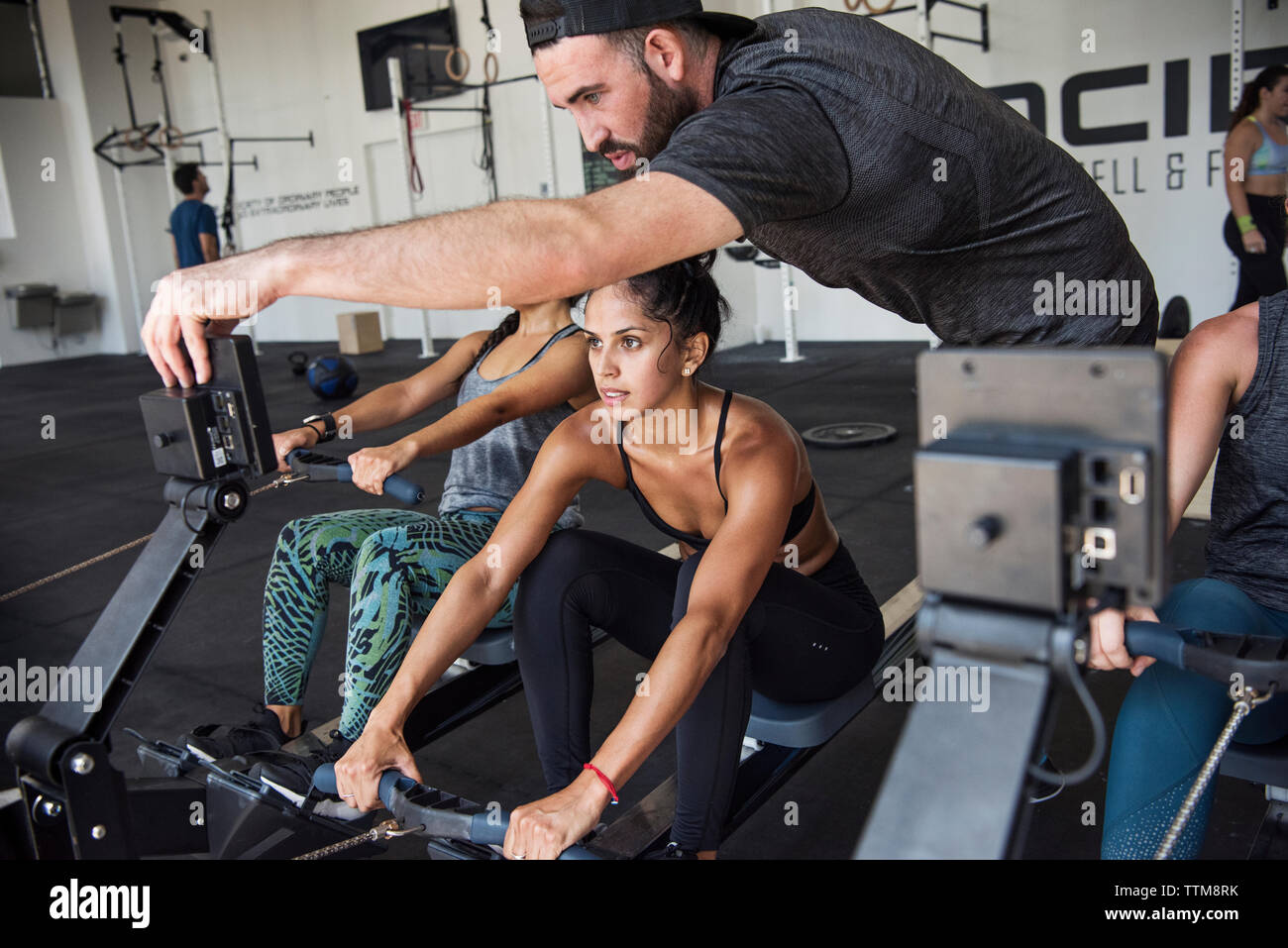 Instructor guiding athletes exercising on rowing machine in crossfit gym - Stock Image