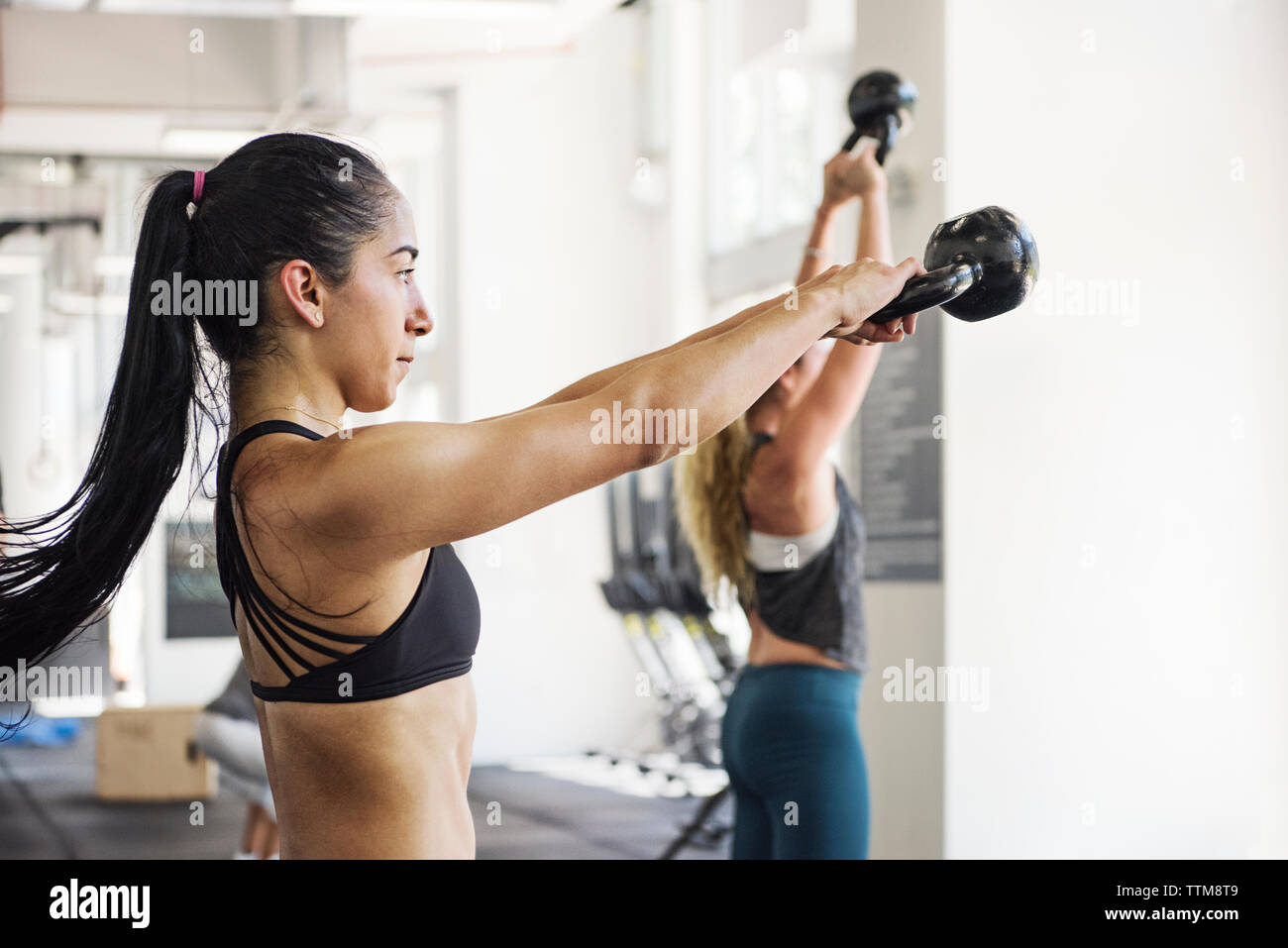 Determined athletes exercising with kettlebells in crossfit gym - Stock Image