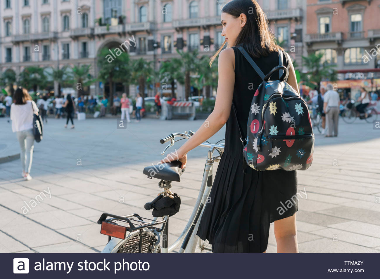 Rear view of woman with bicycle standing on city street Stock Photo
