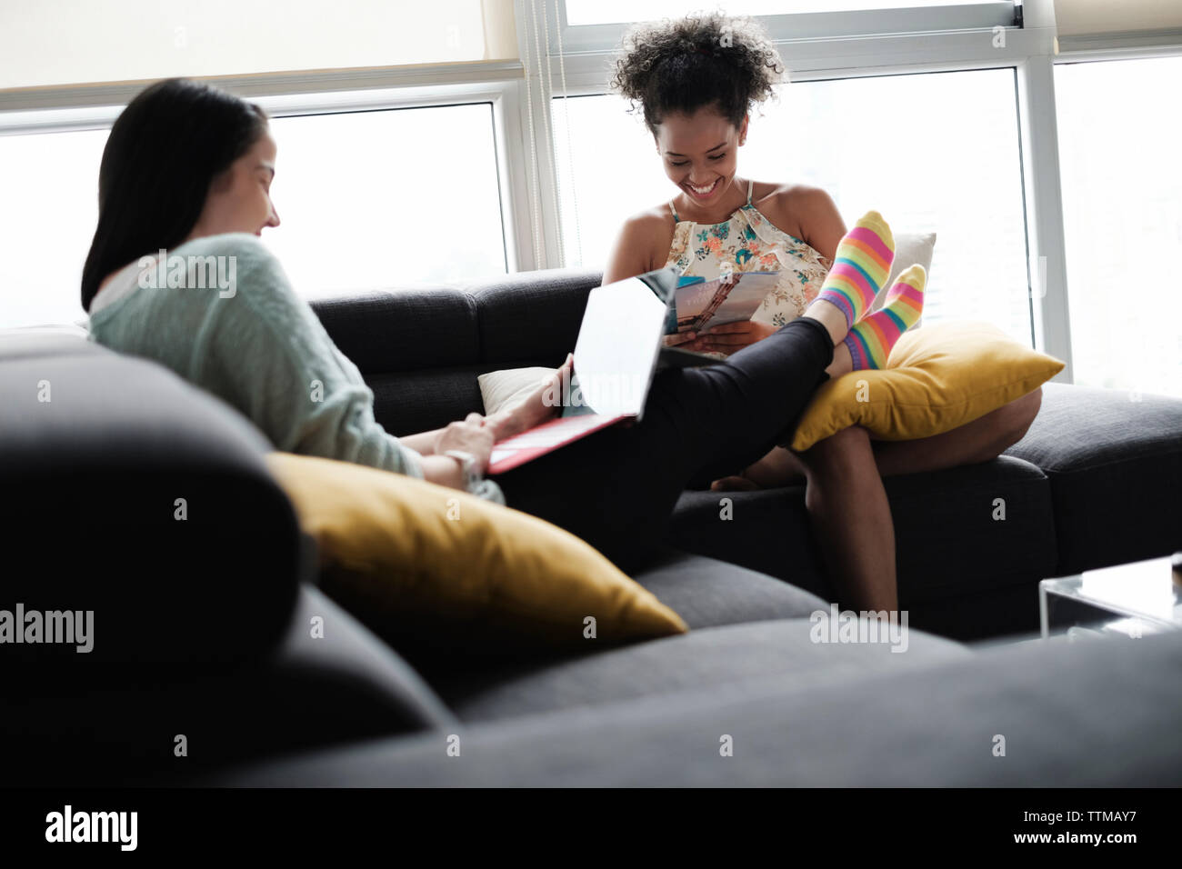 Woman using laptop computer while girlfriend looking at brochures while sitting on sofa in living room - Stock Image
