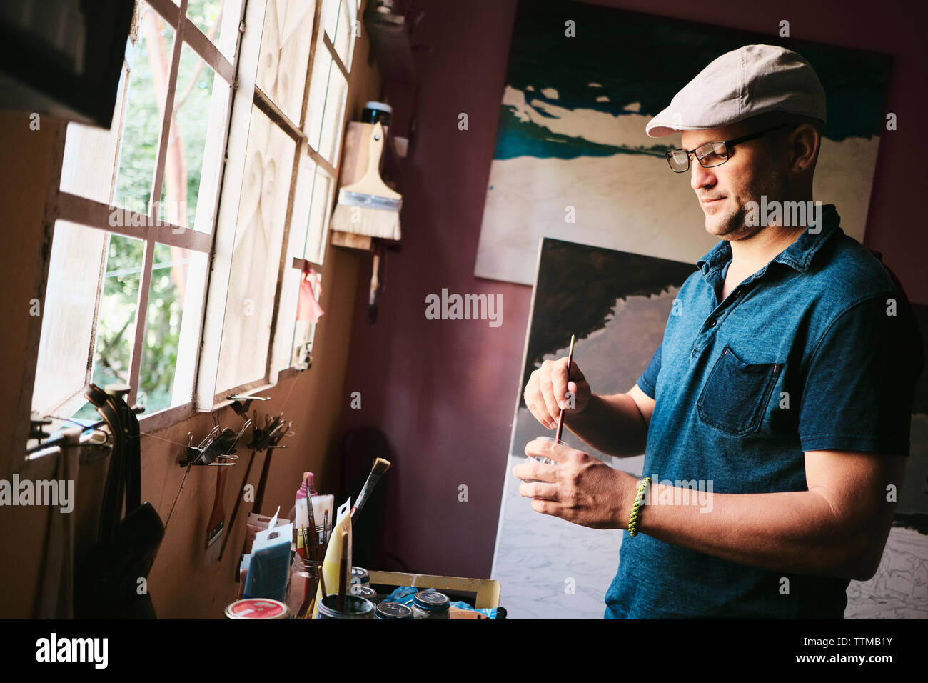 Mid adult male Cuban artist mixing paint with brush in his workshop Stock Photo