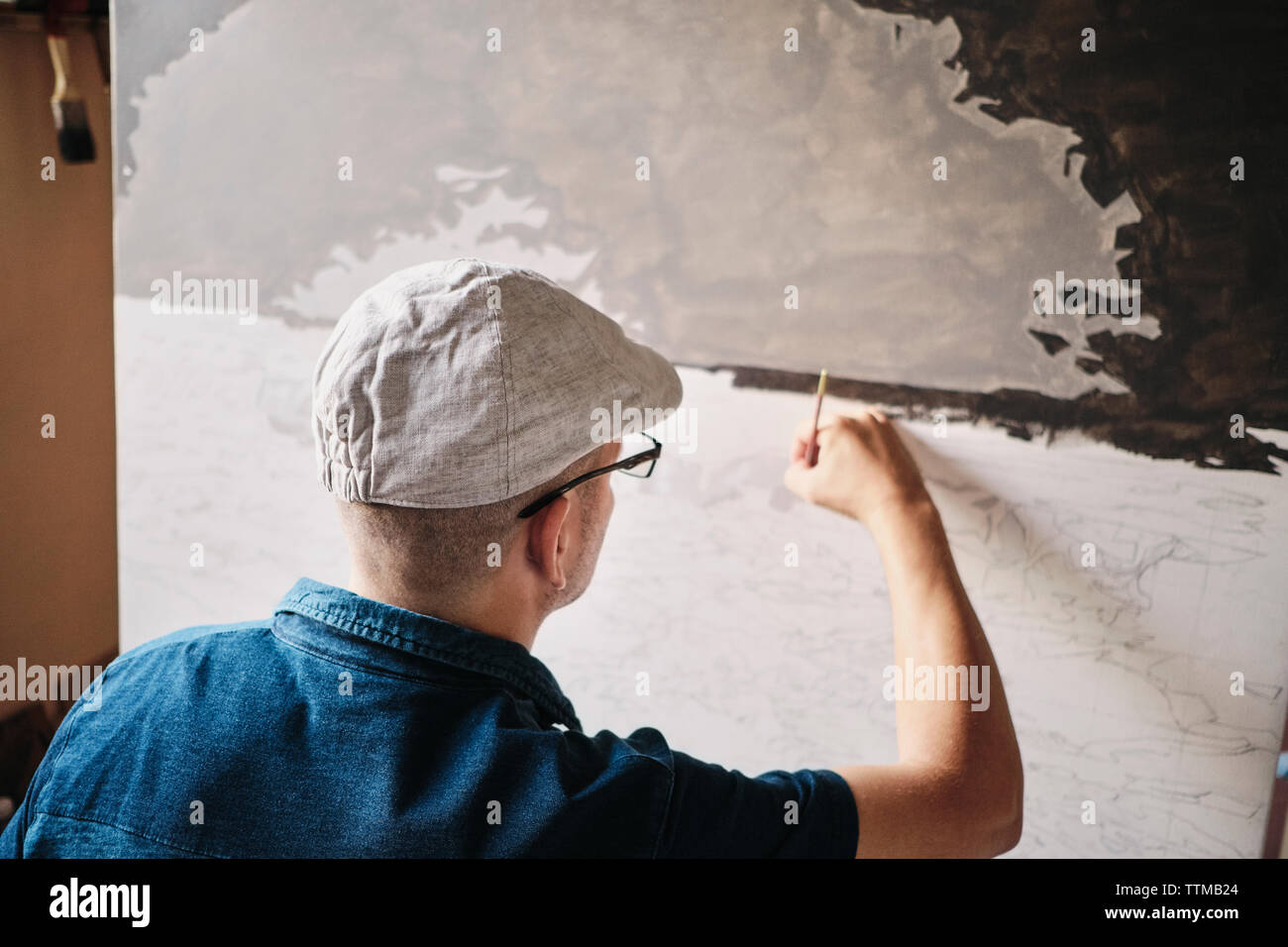 Mid adult Cuban artist painting with brush on canvas in his studio Stock Photo