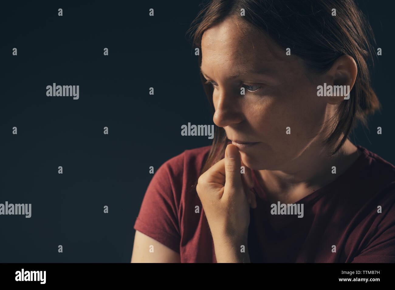 Low key portrait of depressed sad woman - Stock Image