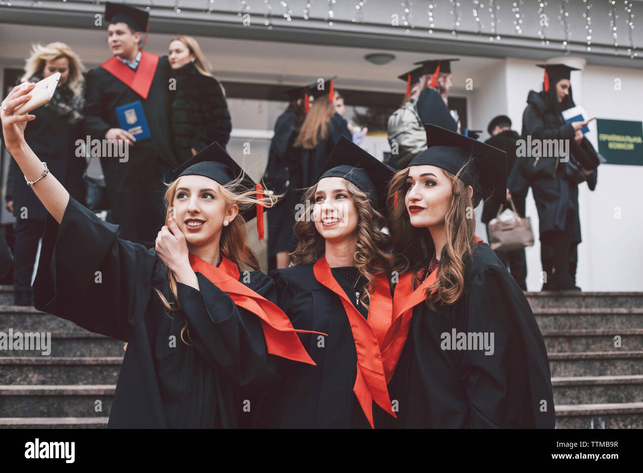 Happy female friends wearing graduation gowns taking selfie while standing on steps - Stock Image