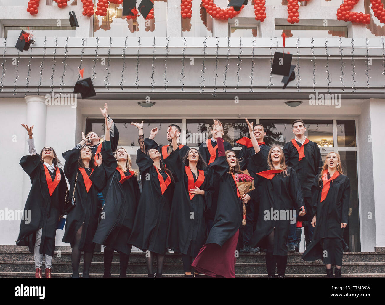 Low angle view of happy students wearing graduation gowns standing on steps by building - Stock Image