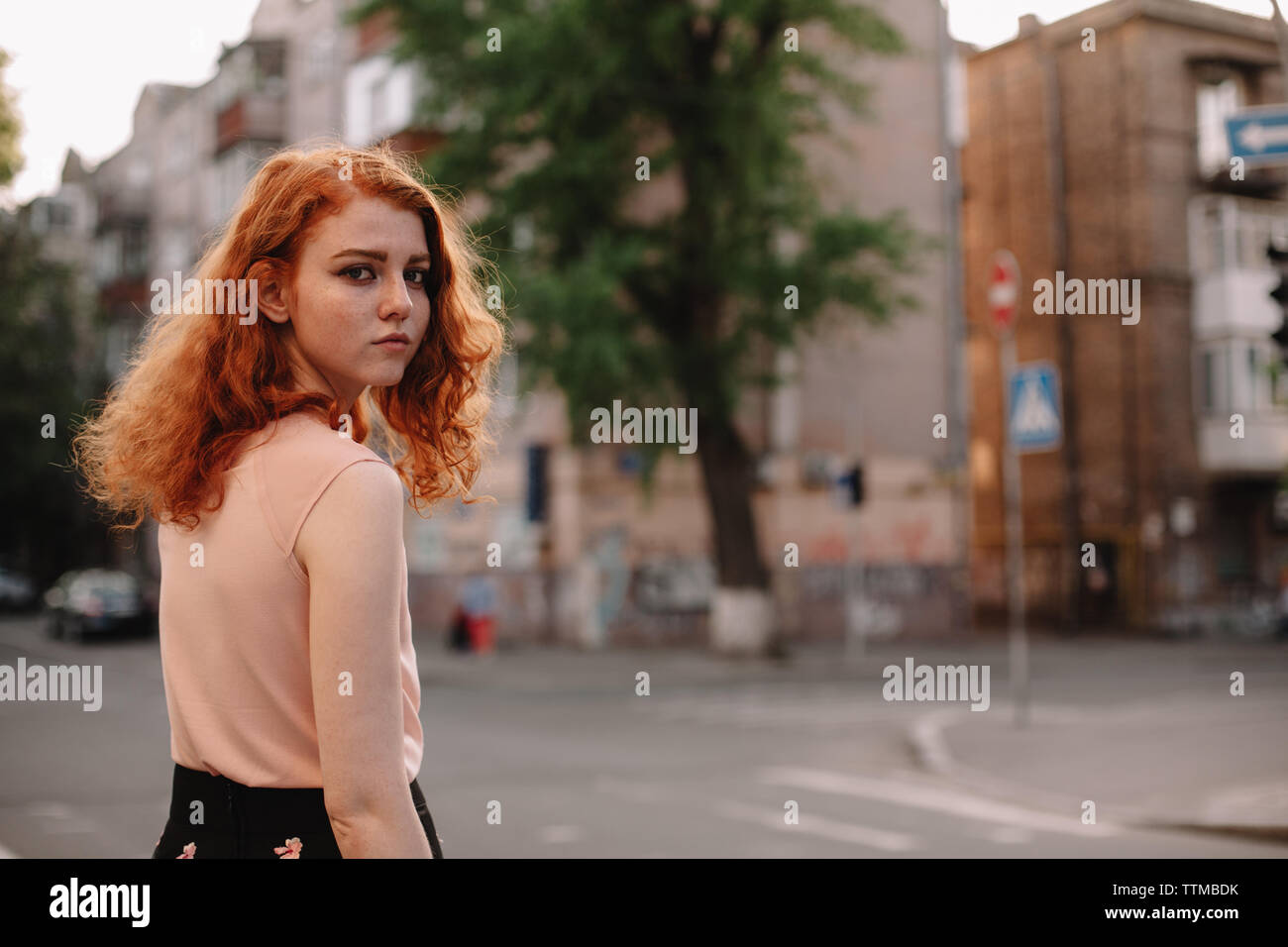 Young redheaded woman walking in city street Stock Photo