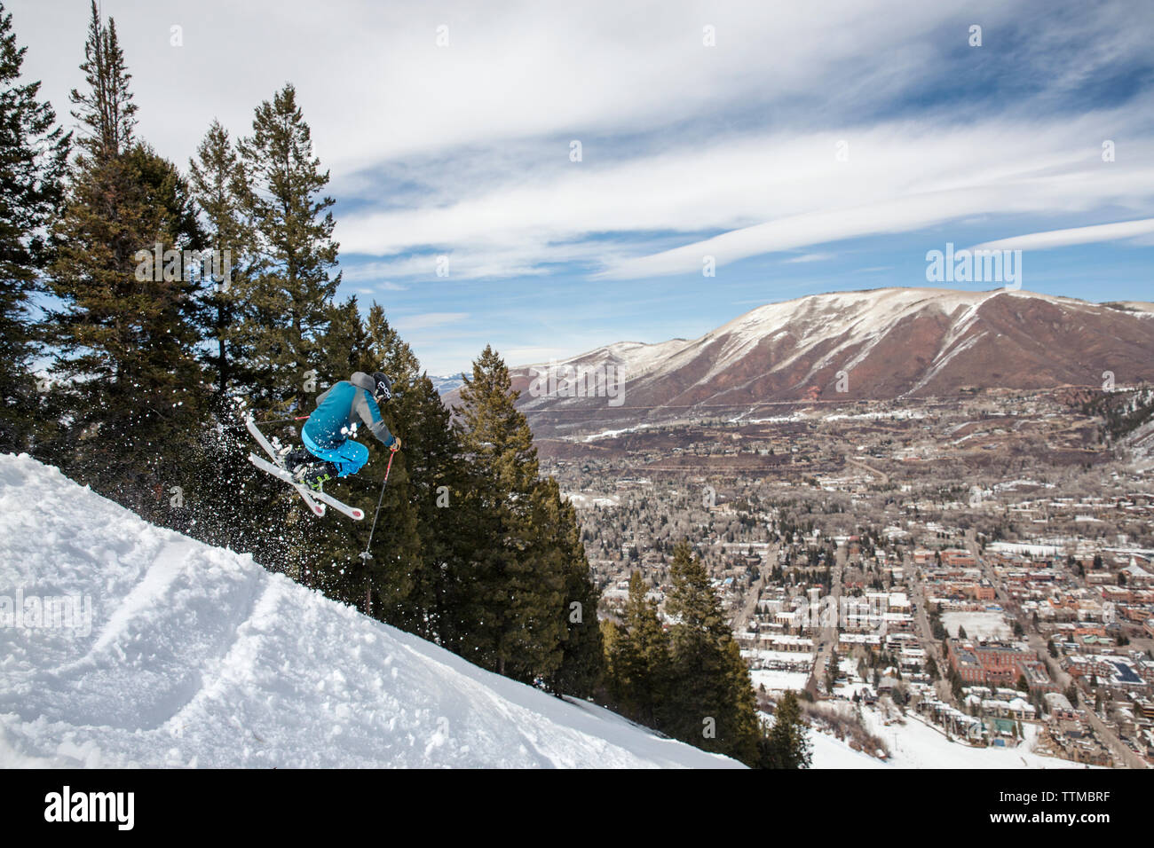 USA, Colorado, Aspen, skier getting air on a trail called Corkscrew with the town of Aspen in the distance, Aspen Ski Resort, Ajax mountain - Stock Image