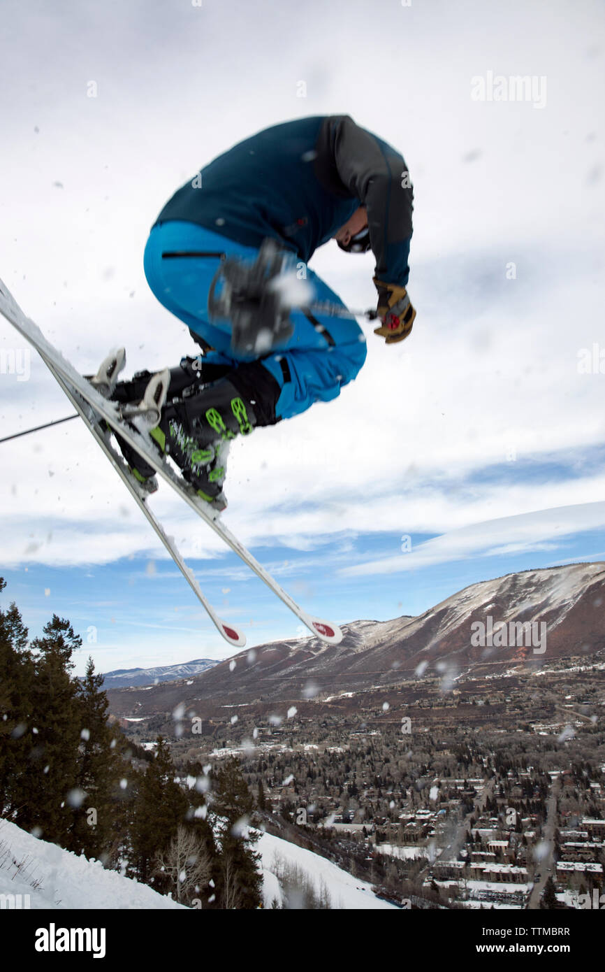 USA, Colorado, Aspen, skier getting air on a trail called Corkscrew with the town of Aspen in the distance, Aspen Ski Resort, Ajax mountain Stock Photo