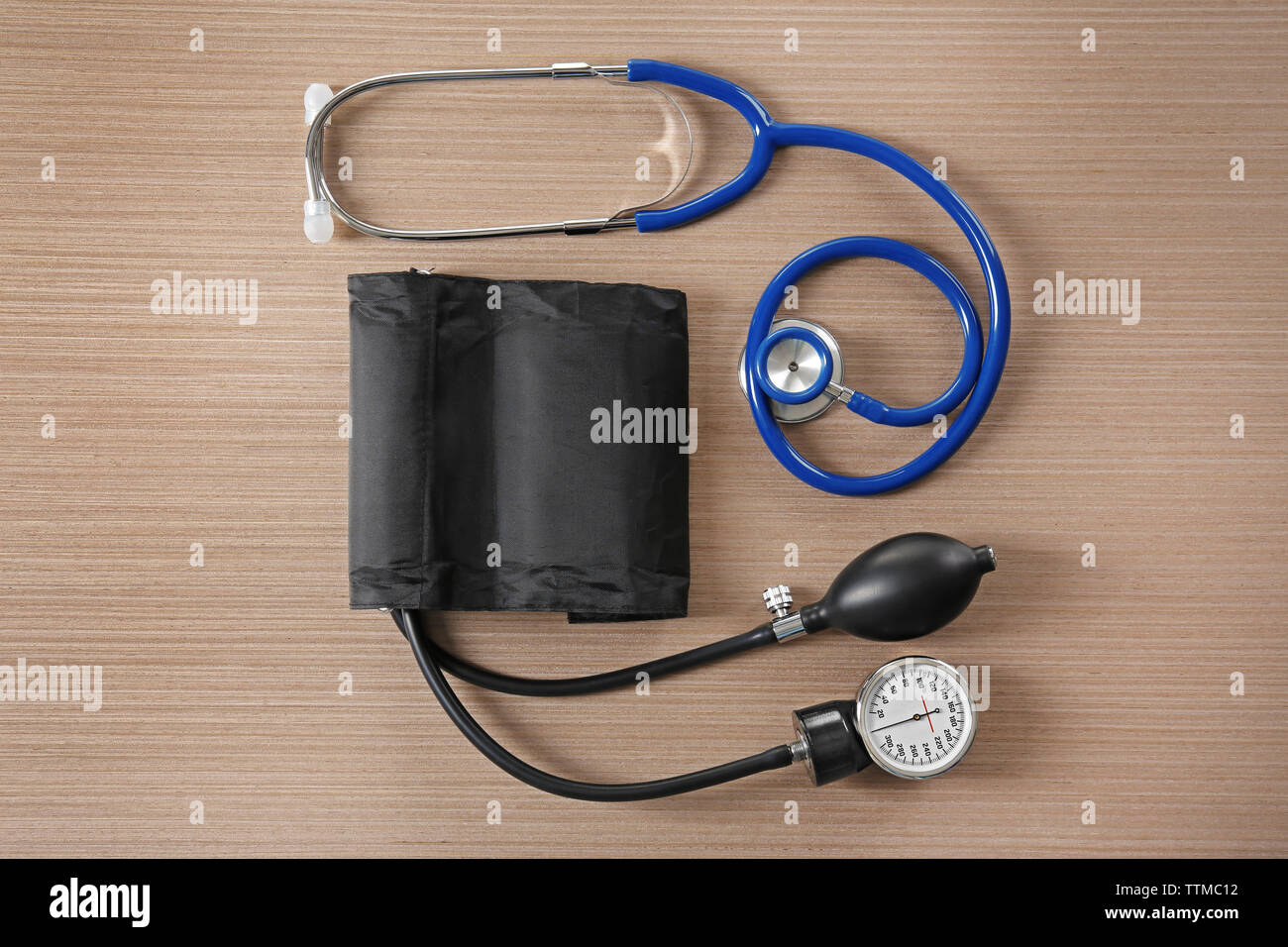 Stethoscope and tonometer on wooden table - Stock Image