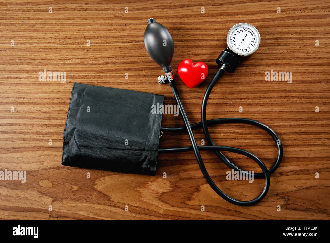 Tonometer with red heart on wooden table - Stock Image