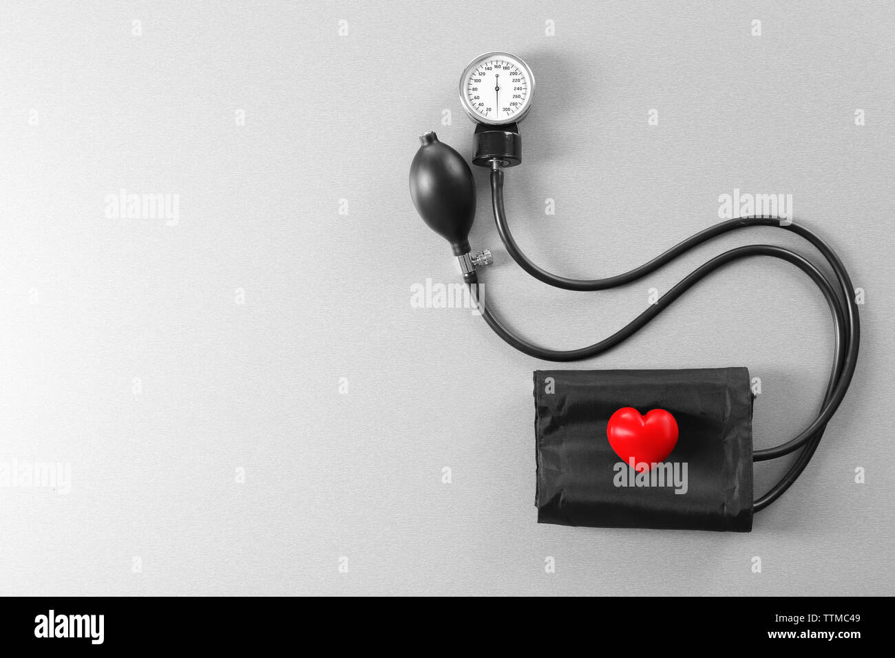 Tonometer with red heart on grey table - Stock Image